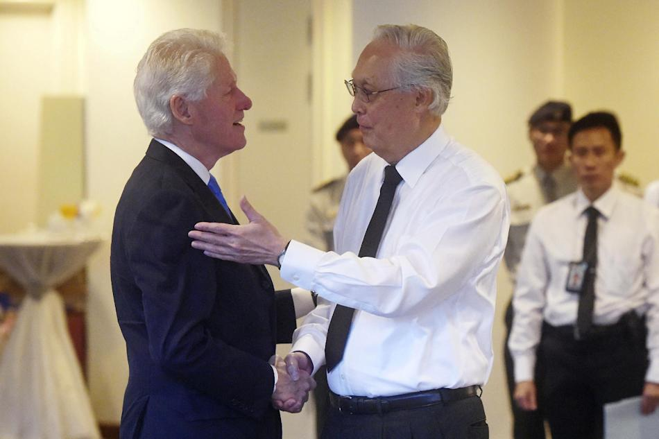 Former U.S. president Bill Clinton, left, is greeted by Singapore emeritus Senior Minister Goh Chok Tong at the state funeral for the late Lee Kuan Yew, at the University Cultural Center,  Sunday, Mar
