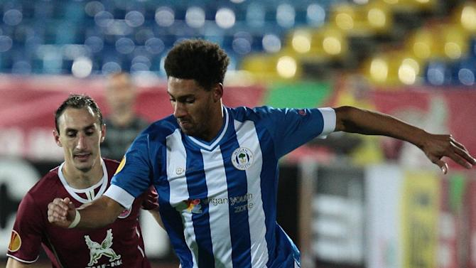 Rubin Kazan's Ruslan Mukhametshin, left, fights for a ball with Wigan Athletic's Ryan Shotton during their Europa League match group D in Kazan, Russia, Thursday Nov. 7, 2013