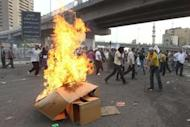 Egyptian protesters set cardboard boxes on fire during an anti-military demonstration outside the defense ministry in Cairo on May 4. Egypt's military prosecution has ordered 179 people be detained over deadly clashes between troops and anti-military protesters in Cairo, a military source told AFP