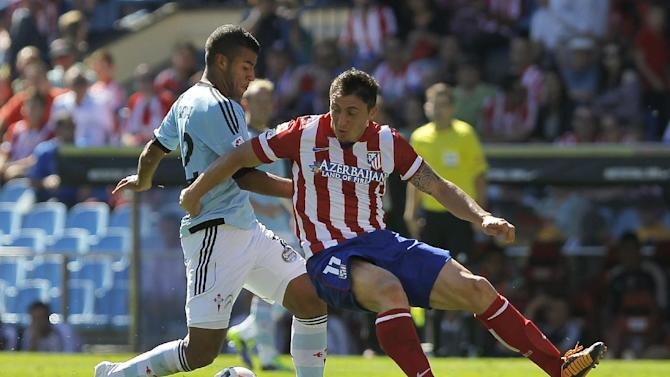 Atletico de Madrid's Cristian Rodriguez from Uruguay, right, in action with Celta de Vigo's Rafinha from Brazil, left, during a Spanish La Liga soccer match at the Vicente Calderon stadium in Madrid, Spain, Sunday, Oct 6, 2013