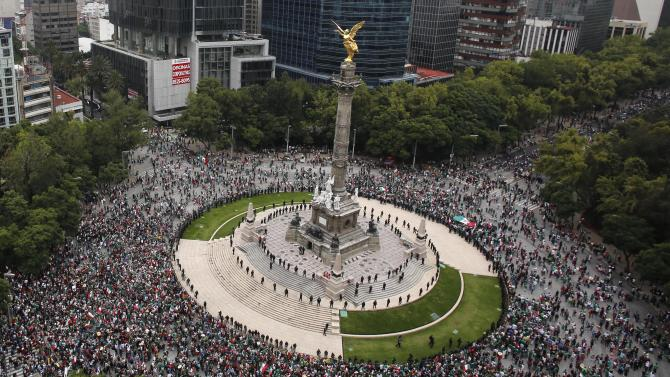 Mexicans celebrate at the Angel of Independence monument in Mexico City after Mexico defeated Brazil in their men's soccer gold medal match during the London 2012 Olympic Games