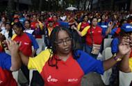 "Supporters of Venezuelan President Hugo Chavez pray during a mass in the center of Caracas on December 11, 2012. Chavez would soon begin a ""post-operative phase"" that would last several days, Nicolas Maduro said in a late Tuesday address to the nation in Caracas. Chavez, 58, flew to Havana for surgery on Monday after revealing that his cancer had returned just two months after his re-election."