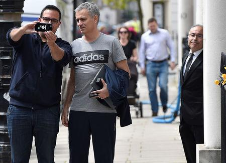 Mourinho poses for a selfie as he walks towards his house in London