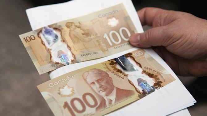 A man holds the new Canadian 100 dollar bills made of polymer in Toronto