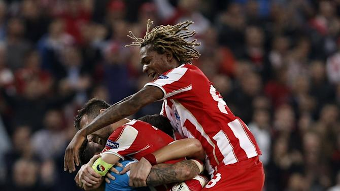 Olympiakos' goalkeeper Roberto, left, celebrates with teammates their team win against Benfica at the end of a Champions League group C soccer match between Olympiakos and Benfica at Karaiskaki stadium, in Piraeus, near Athens, on Tuesday, Nov. 5, 2013
