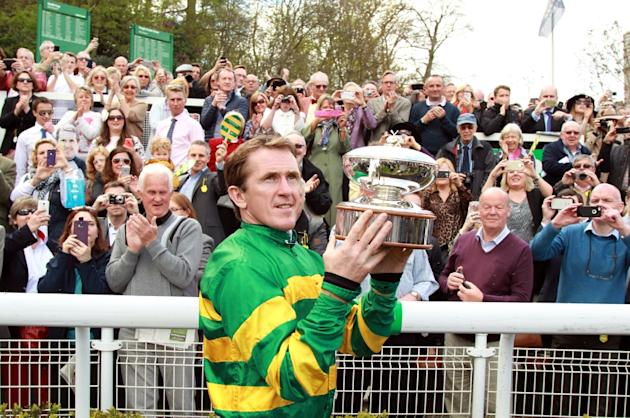 Northern Irish jockey Tony McCoy holds up the jockey championship cup presented to him on his retirement at Sandown Park Racecourse in Esher on April 25, 2015