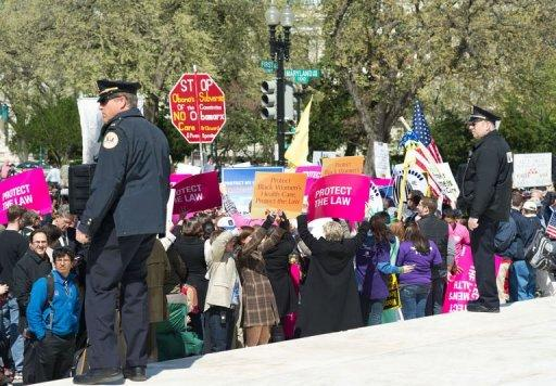 Police officers watch demonstrators outside the US Supreme Court