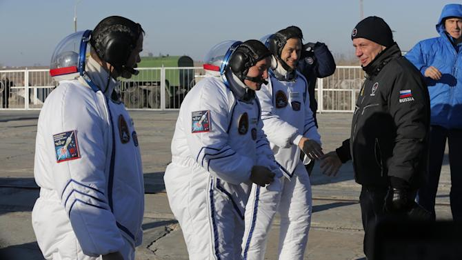 Russia's Space Agency Chief Vladimir Popovkin greets U.S. astronaut Thomas Marshburn, right, Russian cosmonaut Roman Romanenko, center, and Canadian astronaut Chris Hadfield, crew members of the mission to the International Space Station, ISS, prior the launch of Soyuz-FG  rocket  at the Russian leased Baikonur cosmodrome, Kazakhstan, Wednesday, Dec. 19, 2012.  (AP Photo/Dmitry Lovetsky, pool)