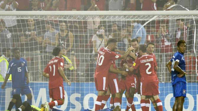 Canadian players celebrate their third goal against Belize keeper Kosuke Kimur during the second half of a FIFA World Cup qualifying soccer match Friday, Sept. 4, 2015, in Toronto. (Jon Blacker/The Canadian Press via AP) MANDATORY CREDIT