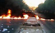 "A Shaam News Network image is said to show a street blocked with burning tires during an anti-regime demonstration in Damascus on Thursday. UN chief Ban Ki-moon has warned that Syria risks a ""catastrophic civil war"" following a massacre that sparked global outrage, as the US slammed Russia for resisting UN action against Damascus"