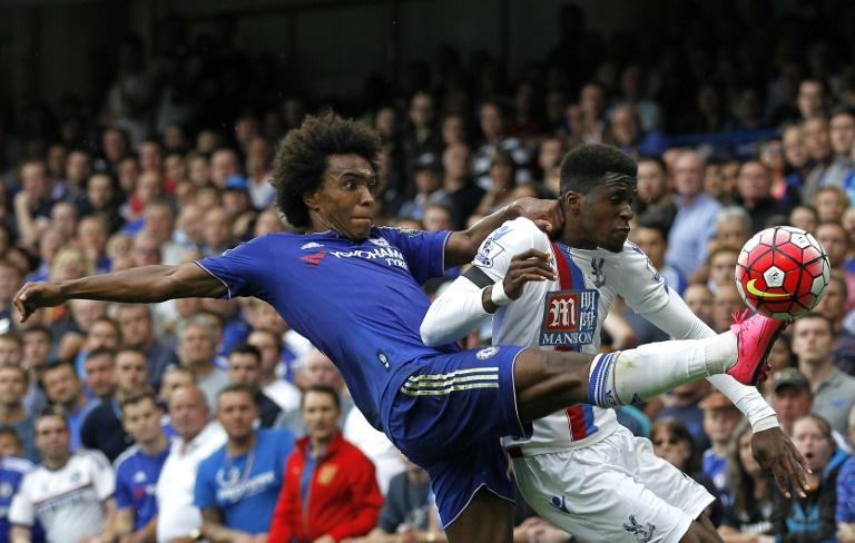 Chelsea's Brazilian midfielder Willian (L) challenges Crystal Palace's Ivorian-born English striker Wilfried Zaha during the English Premier League football match at Stamford Bridge in London on Augus