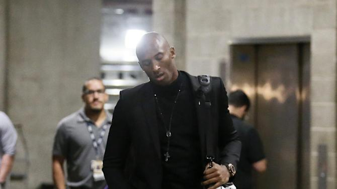 Los Angeles Lakers' Kobe Bryant arrives at Staples Center before the NBA basketball game against the Toronto Raptors  in Los Angeles, Sunday, Dec. 8, 2013. Bryant is expected to make  his long-awaited return from a torn left Achilles tendon injury from April 12th