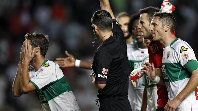 Elche's players protest to referee Muniz Fernandez during their La Liga soccer match at the Martinez Valero stadium in Elche, Spain, Wednesday, Sept. 25, 2013