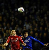 Liverpool's English forward Andy Carroll (L) and Everton's Belgian midfielder Marouane Fellaini jump for the ball during the English Premier League football match between Liverpool and Everton at Anfield in Liverpool. Liverpool won 3-0
