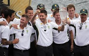 Australian cricket team captain Michael Clarke (C) holds aloft a replica Ashes urn and a crystal trophy as he celebrates with team mates during a public celebration ceremony at the Sydney Opera House January 7, 2014. REUTERS/David Gray/Files