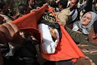 Palestinian mourners carry the body of 12-year-old schoolboy Ayoub Asalya, during his funeral in Jabalyia refugee camp in the northern Gaza Strip. New Israeli air strikes on the Gaza killed three Palestinians on Sunday, raising the death toll in a latest round of violence to 18, as militants fired over 120 rockets into Israel