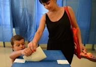 A Romanian woman casts her ballot in Romania's presidential impeachment referendum. Romania's President Traian Basescu was suspended after a procedure launched by his rivals in the centre-left USL coalition that has been in power for three months