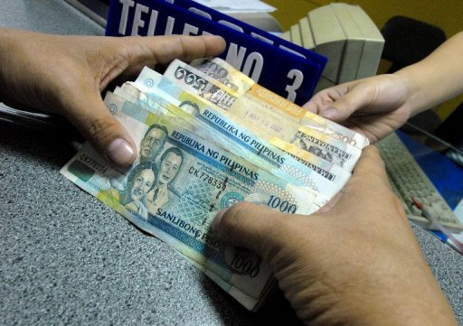 A customer holds Philippine peso notes during a bank transaction in Manila. The Philippine central bank has trimmed its key interest rates by a further 25 basis points, saying the domestic economy needs a further boost to override weak global demand
