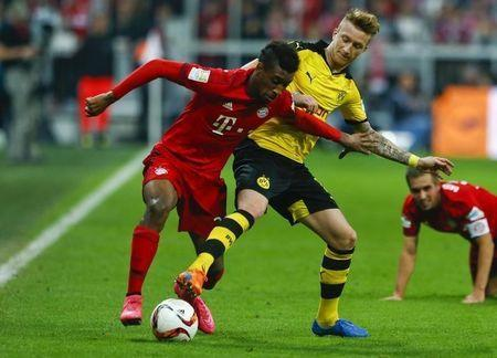 Bayern Munich's Coman fights for the ball with Borussia Dortmund's Reus during their German first division Bundesliga soccer match in Munich