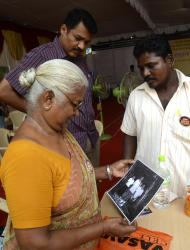 In this Monday Oct.10, 2011, photo, Arputhammal , the mother of Arivu Perarivalan, one of the three convicted in the 1991 assassination of former Indian Prime Minister Rajiv Gandhi, looks at his photo in Chennai, India. Across most of India the three men on death row in the assassination of Gandhi are reviled as murderous traitors to the nation. But ethnic Tamils in southern India see things very differently. Nearly every major public figure has demanded clemency, sparking a political storm fueled by emotions still raw from the gory 2009 routing of Sri Lanka's Tamil rebels, who ordered the killing. ( AP Photo/ Nathan G.)