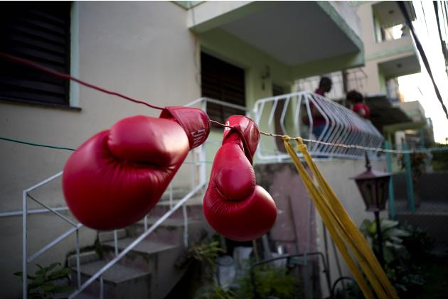 In this Jan. 19, 2017 photo, Idamelys Moreno's boxing gloves hang on a line to dry, after a training session in Havana, Cuba. Women were first allowed to box at the Olympics during the 2012 Summer
