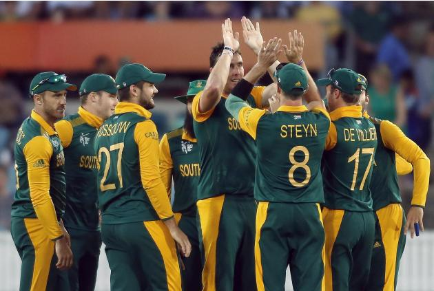 South Africa's Kyle Abbott celebrates with teammates after dismissing Ireland's Gary Wilson LBW for a duck during their Cricket World Cup match at Manuka Oval in Canberra