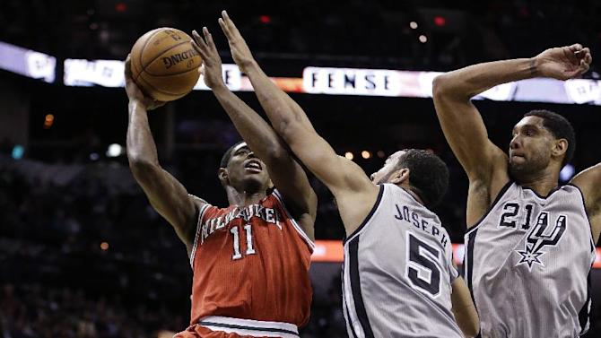 Milwaukee Bucks' Brandon Knight (11) is pressured by San Antonio Spurs' Cory Joseph (5) and Tim Duncan (21) during the second half of an NBA basketball game, Sunday, Jan. 19, 2014, in San Antonio. San Antonio won 110-82