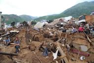 Earthquake victims sit amid the debris of collapsed houses in Ludian county in Zhaotong, in southwest China's Yunnan province on August 4, 2014