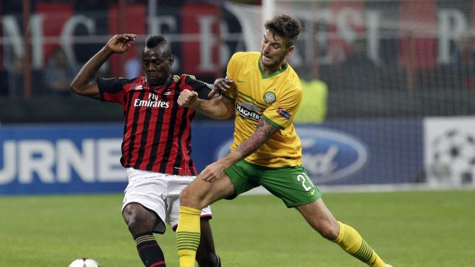 AC Milan's Mario Balotelli and Celtic's Charlie Mulgrew fight for the ball during their Champions League Group H soccer match at San Siro stadium in Milan