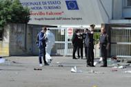 Policemen inspect the scene after a blast near a school in Brindisi. A 16-year-old girl died and five other teens were gravely injured in a powerful bomb blast outside their school named after a woman killed by the mafia with her judge husband in 1992