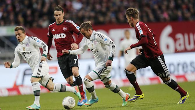 Nuremberg's Nick Weber, right, and Nuremberg's Markus Feulner, 2nd left, and Bayern's Mario Goetze challenge for the ball during a  German first division Bundesliga soccer match  between 1.FC Nuremberg and Bayern Munich in Nuremberg, Germany, Saturday, Feb. 8, 2014