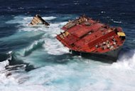 This file photo, released by Maritime New Zealand in April, shows the Liberian-flagged container ship 'Rena,' stuck on Astrolabe Reef as it is pounded by high seas off the coast of Tauranga. The captain and second officer of the ship that caused N.Zealand's biggest sea pollution disaster have both been jailed for seven months