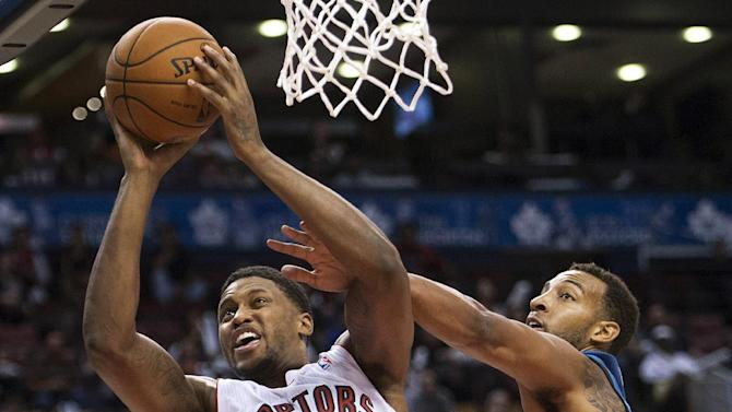 Toronto Raptors forward Rudy Gay, left, drives past Minnesota Timberwolves Derrick Williams during the first half of an NBA preseason basketball game in Toronto on Wednesday, Oct. 9, 2013