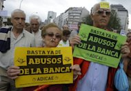 "People hold placardds reading ""Enough with Bank abuses"" during a demonstration June 2, in Coruna. Spain's weak banks need at least 40 billion euros (US$50 billion) in new capital to strengthen against severe financial shocks, the International Monetary Fund said"