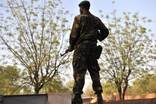 """A Malian soldier stands guard at Kati military camp near Bamako. The UN Security Council called for an immediate ceasefire and return to democracy in Mali, prompting an announcement of an end to """"military operations"""" by Tuareg rebels in the north."""