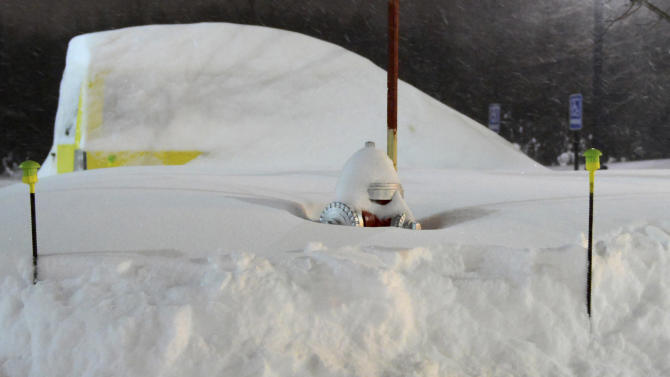 Drifted snow shrouds a fire hydrant and car early Saturday morning Feb. 9, 2013, after a heavy overnight snowfall and winds in Hadley, Mass. (AP Photo/Springfield Republican, Michael Beswick)