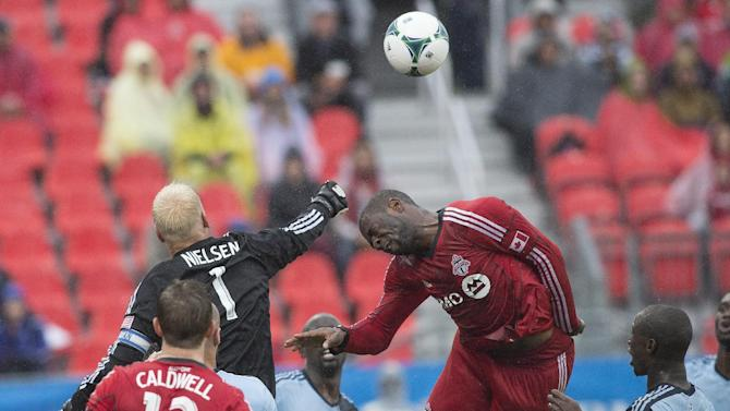 Sporting Kansas City's goalkeeper Jimmy Nielsen punches clear from Toronto FC's Bright Dike during the first half of an MLS soccer game in Toronto on Saturday, Sept, 21, 2013