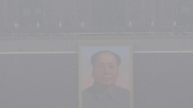 Chinese security personnel march in thick haze near the portrait of former Chinese leader Mao Zedong in Beijing Tuesday, Jan. 29, 2013. Extremely high pollution levels shrouded eastern China for the second time in about two weeks Tuesday, forcing airlines in Beijing and elsewhere to cancel flights because of poor visibility and prompting government warnings for residents to stay indoors. (AP Photo/Ng Han Guan)