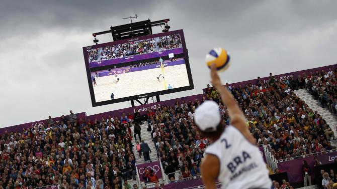 Spectators watch as Brazil's Emanuel serves against Poland's Prudel and Fijalek during their men's quarterfinals beach volleyball match at Horse Guards Parade during the London 2012 Olympic Games