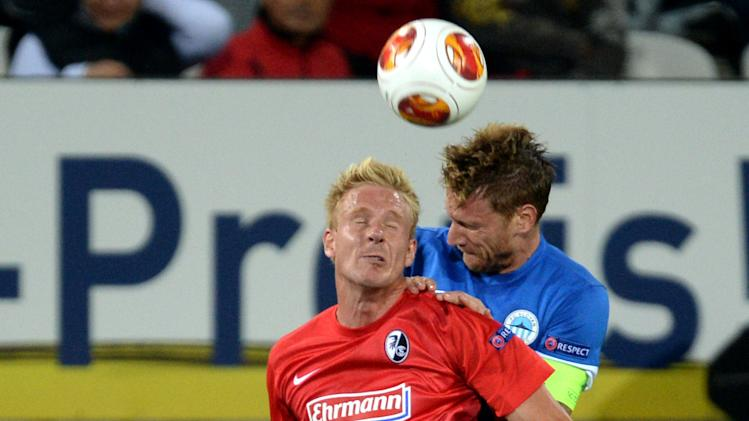 Mike Hanke , left, of Freiburg and Radoslav Kovac  of Liberec  challenge for the ball during the UEFA Europa League Group H  soccer match between SC Freiburg and Slovan Liberec FC  in Freiburg, Germany,  Thursday Sept. 19, 2013