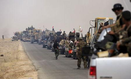 Shi'ite paramilitaries riding military vehicles travel from Lake Tharthar toward Ramadi to fight against Islamic state militants, west of Samarra