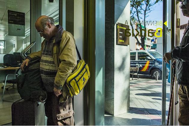 Jose Antonio Garcia Mendoza, 64, left, waits with his belongings outside a Bankia bank to request a loan after his eviction from the same bank in Madrid, Spain on Tuesday, April 28, 2015. Maria Montie