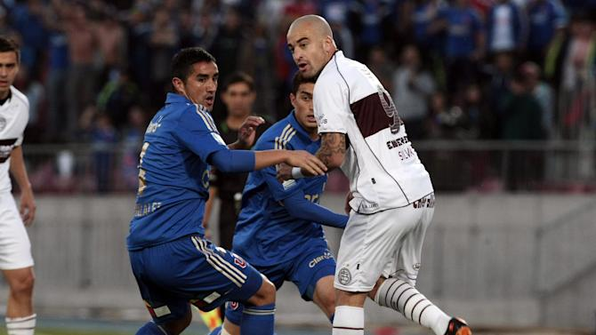 Chile's Universidad de Chile's Osvaldo Gonzalez, right, and Argentina's Lanus' Santiago Silva, go for the ball during a Copa Sudamericana soccer match in Santiago, Chile, Wednesday, Sept. 25, 2013
