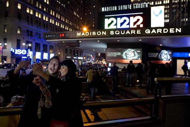 "Friends Steve Ramos, of Los Angeles, and Viviana Barraza, of Bridgeport, Conn., take a photo of themselves before attending the ""12-12-12"" benefit concert at Madison Square Garden in New York Wednesda"