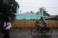 """This file photo shows local residents passing a mosque in Sittwe, capital of Myanmar's western Rakhine state. Buddhist villagers fled their homes Saturday as renewed sectarian violence hit western Myanmar, officials said, blaming Muslim Rohingya people from a """"neighbouring country"""" for the unrest"""