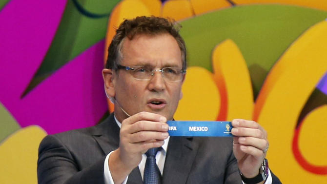 "FIFA Secretary General Jerome Valcke holds the slip showing ""Mexico"" during the draw for the 2014 World Cup at the Costa do Sauipe resort in Sao Joao da Mata"