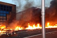 A picture taken by a member of the public shows flames on a road following the crash of a helicopter in central London on January 16, 2013. Two people were killed after a helicopter hit a crane at a building site in central London and plunged to the ground in a ball of flames on Wednesday, police said