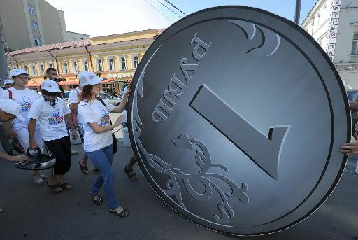"Members of a social network group ""I Really Like Putin"" perform in front or a two-meter Russian Ruble coin in Moscow on August 18, 2011, during their action in support of Russia's currency"