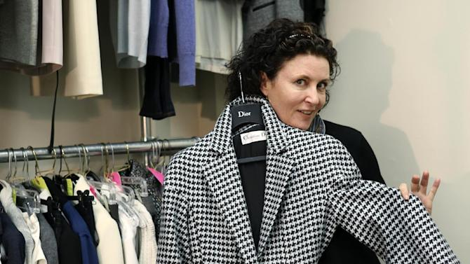 "In this Nov. 11, 2013 image released by ABC, costume designer Lyn Paolo holds a Christian Dior coat worn by actress Kerry Washington for the ABC drama series, ""Scandal,"" in the show's wardrobe closet on the Sunset Gower lot in the Hollywood section of Los Angeles. The series, about a Washington fixer, airs Thursdays at 10 p.m. EST. (AP Photo/ABC, Danny Feld)"