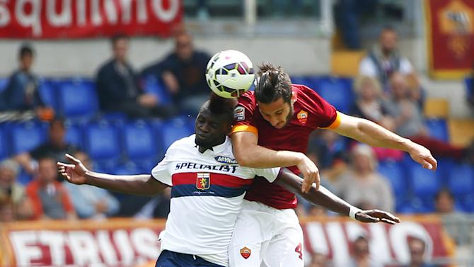 AS Roma's Kostantinos and Genoa's Niang jump for the ball during their Italian Serie A soccer match at the Olympic stadium in Rome